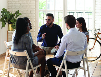 Male psychologist therapist speak at group therapy session helping